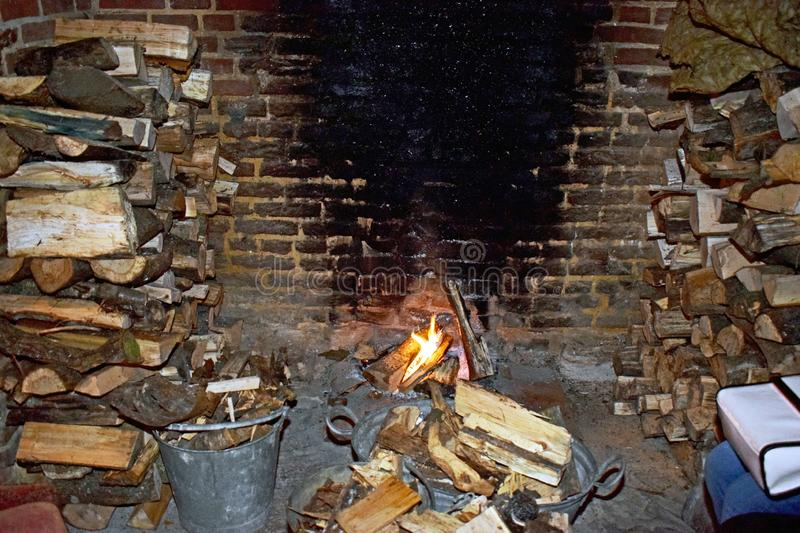 A brick fireplace. A brick fire place with logs stack either side ready to go on the fie, there is a fire burning logs in the hearth and a silver steel bucket stock image