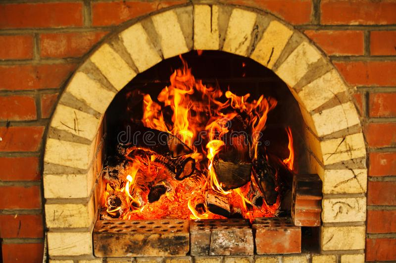 Brick fireplace with burning fire, red flame from woods. Warm comfortable place with orange flame, hot logs, decoration in house interior stock photos