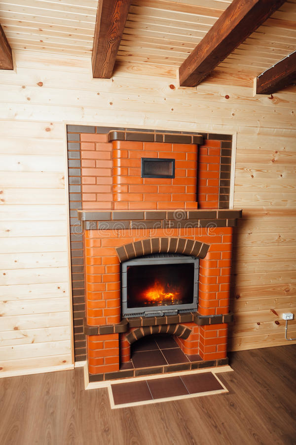 Brick fireplace in wooden house. Closeup view stock photo