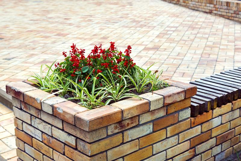 Brick flowerpot for flowers and benches. Brick flowerpot for flowers and benches on the background of a pedestrian square for walking in the city stock image