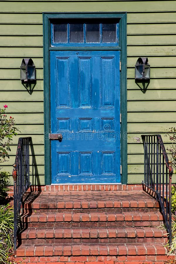 Bright painted blue door on a green house with brick steps royalty free stock image