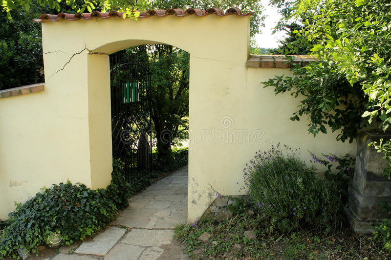 Brick Gateway in the garden. Lavender, beige and yellow, trees and bush, door royalty free stock photos