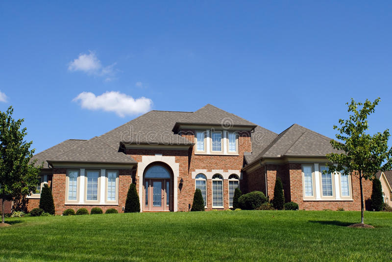 Brick House. Modern brick house with front lawn and blue sky royalty free stock photos