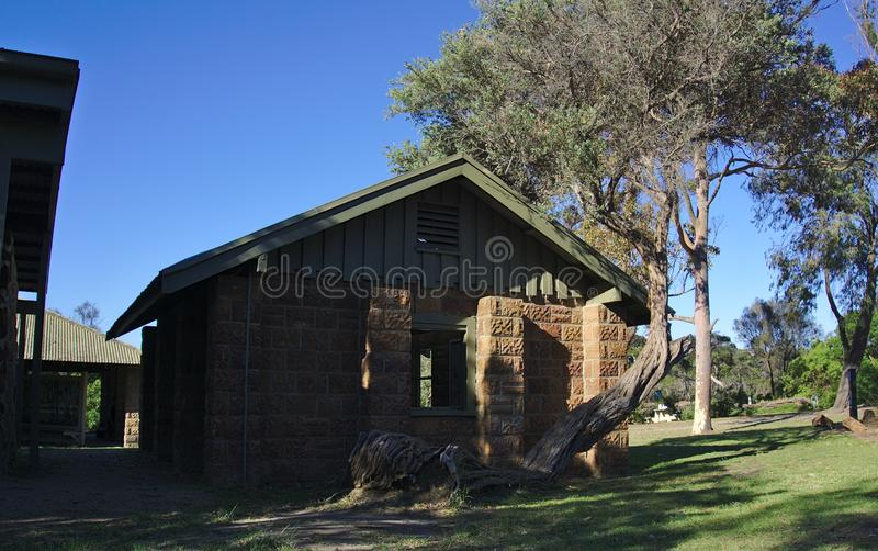 Brick house in forest. With tilted tree in front side stock photography