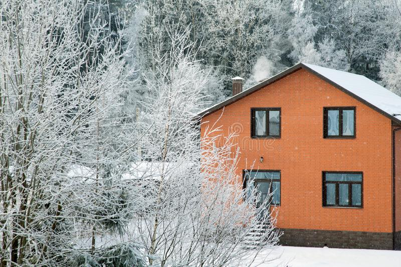 Brick house on a frosty winter day. Among the trees royalty free stock photo