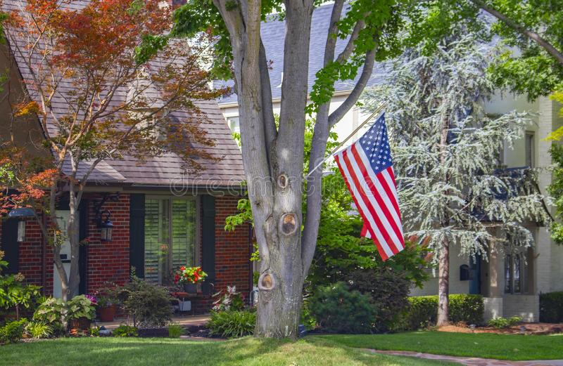 Brick house set in traditional neighborhood with large trees a bird feeder and colorful flowers and an American flag stock photography