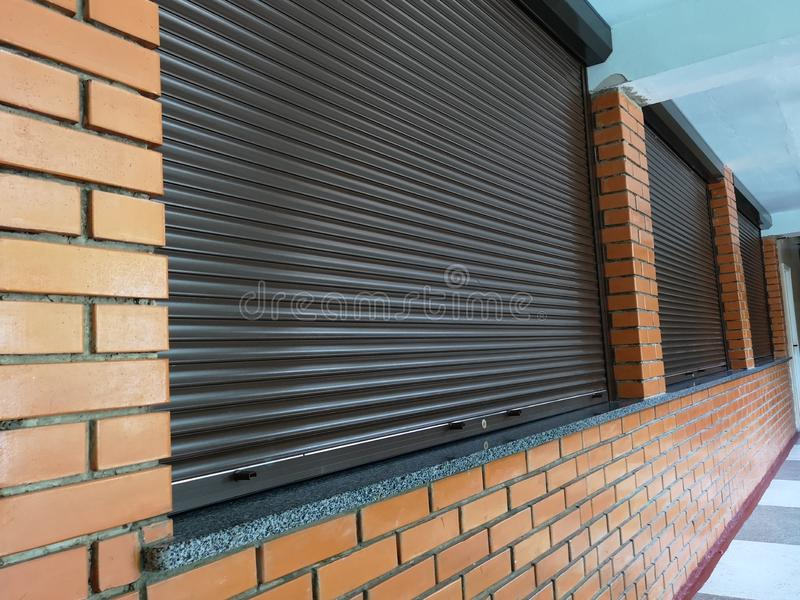 Brick House Windows with rolling shutter for house protection. Photo, home, safety, roller, blind, exterior, louvers, outdoor, outside, frame, security, antifa royalty free stock photos