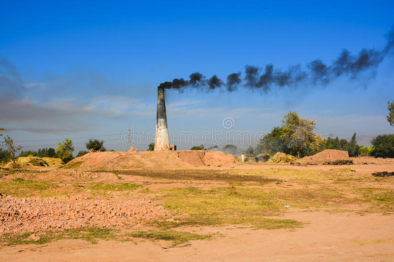 Brick Kiln. Smoke coming from chimney of a brick kiln somewhere near Shadia Mianwali – Punjab, Pakistan royalty free stock image