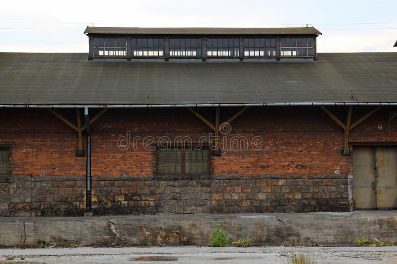Brick old vintage retro warehouse with rusty doors, street view.  royalty free stock photography