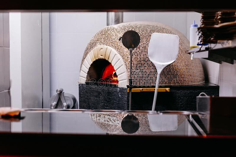 Brick oven with fire for making Italian pizza in the kitchen stock photos