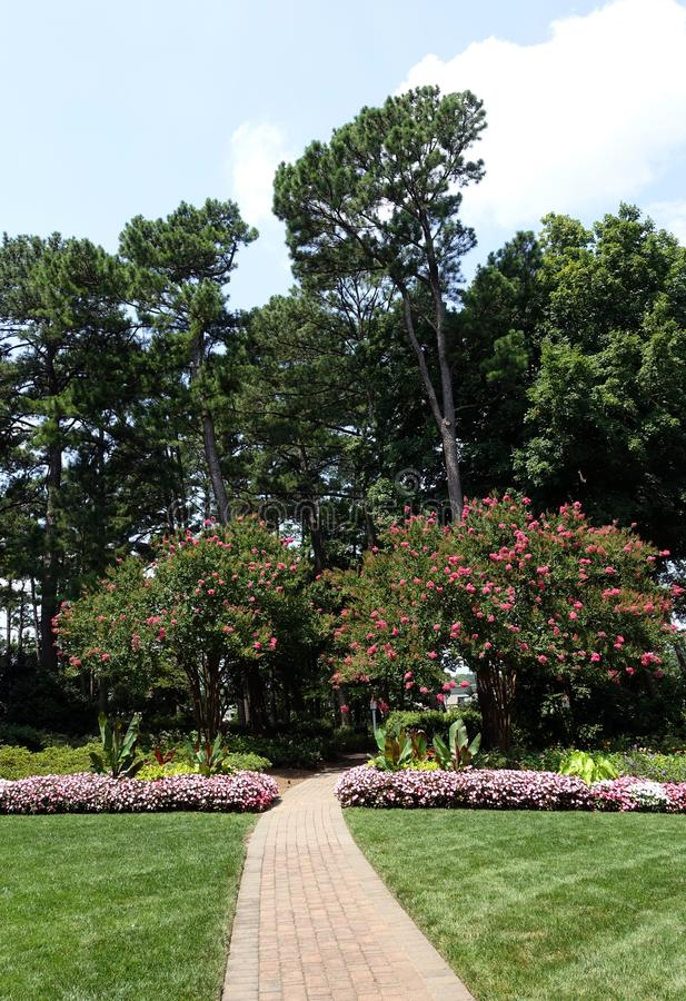 A Brick Path Leads  into a Garden in Raleigh, North Carolina. A Brick Path leads from Blossoming Gardens into the Woods in Raleigh, North Carolina royalty free stock photos