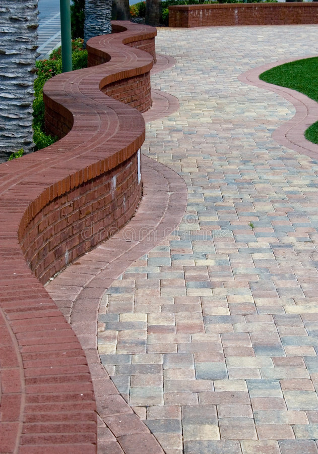 Brick Pathway. Winding brick pathway with low brick wall snaking along path royalty free stock image