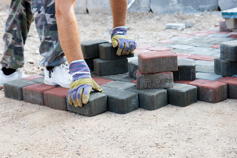 Brick pave. Worker pave a new road royalty free stock photography
