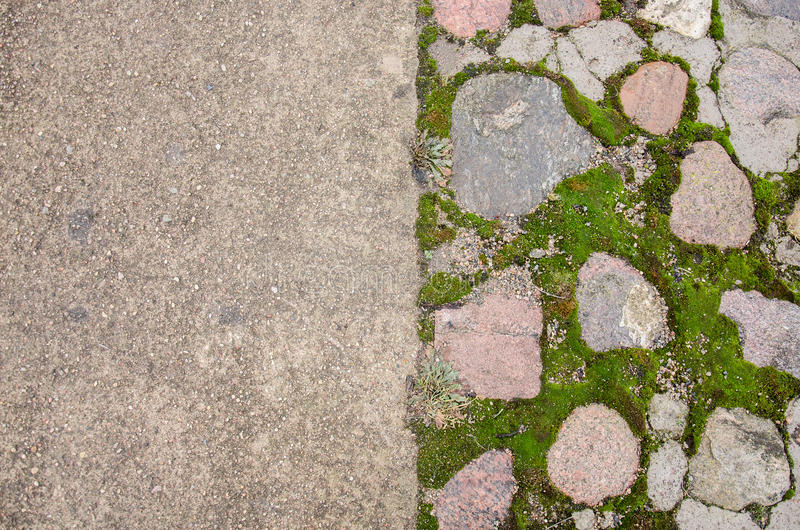 Brick pavement blocks. Cobbled pavement. Green moss on old stone footpath. Road pavement, grass green. Moss trying to grow inbetwe stock photo