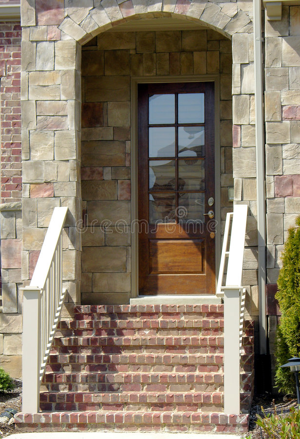 Brick Porch. Brick steps leading to a stone porch and exterior door to a home stock photography