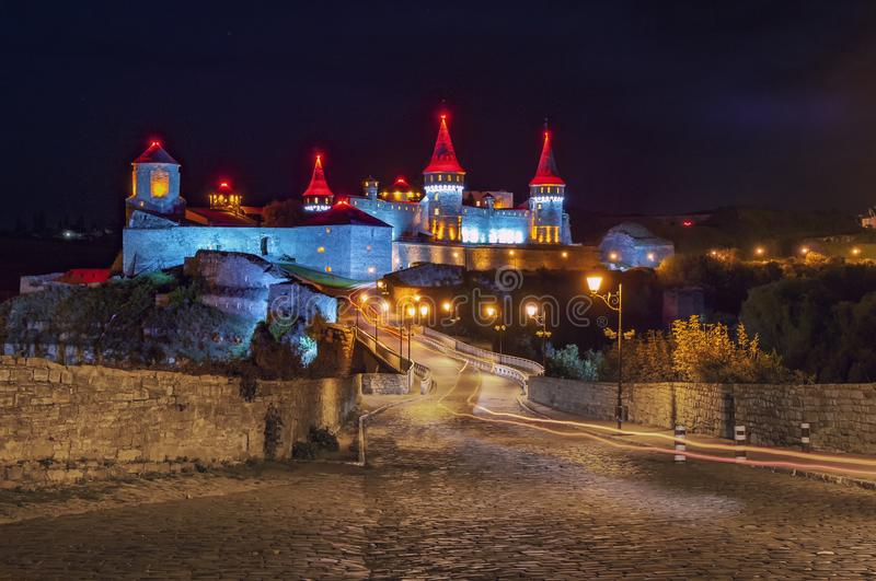 Brick road to ancient castle at night. Amazing medieval fortress stock image
