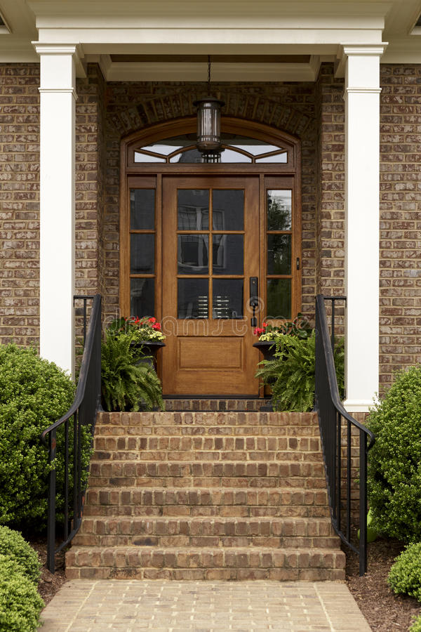 Brick Staircase Leading Up To A Brown Front Door Stock