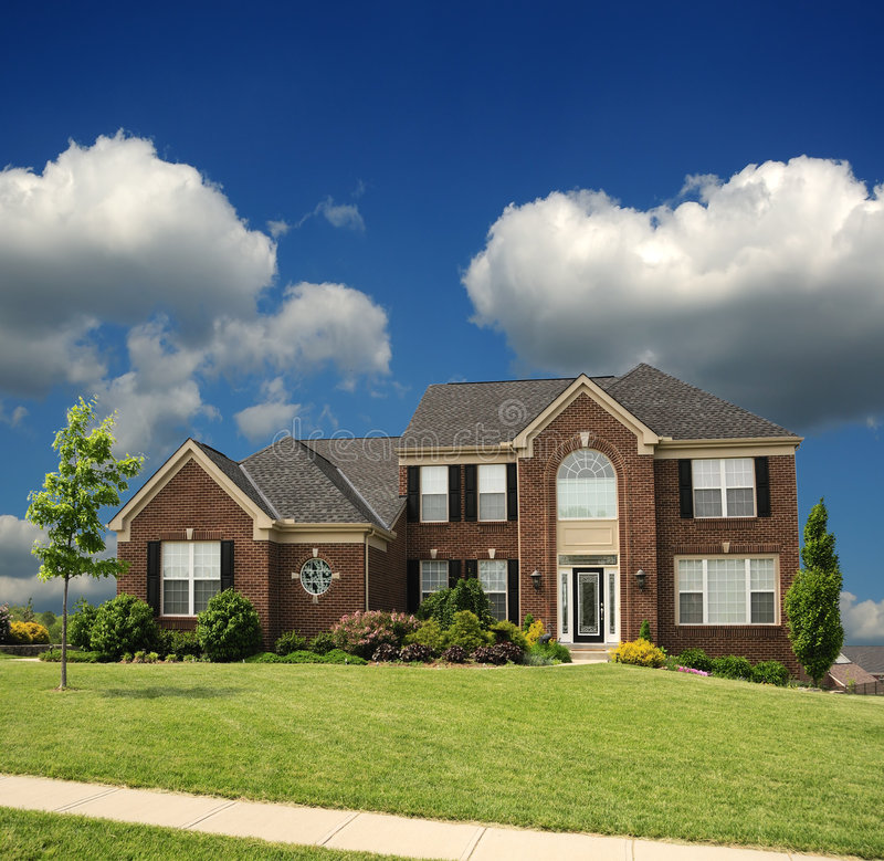 Brick Suburban 2-Story Home. On a sunny, cloudy summer day royalty free stock images