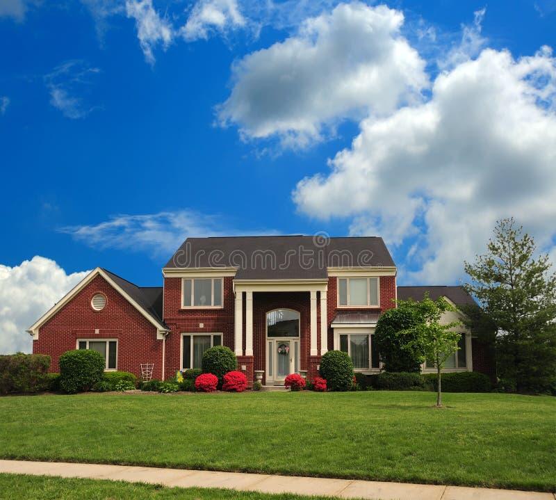 Brick Suburban Home On A Hillside. Brick Suburban Home on a hill on a sunny summer day stock image