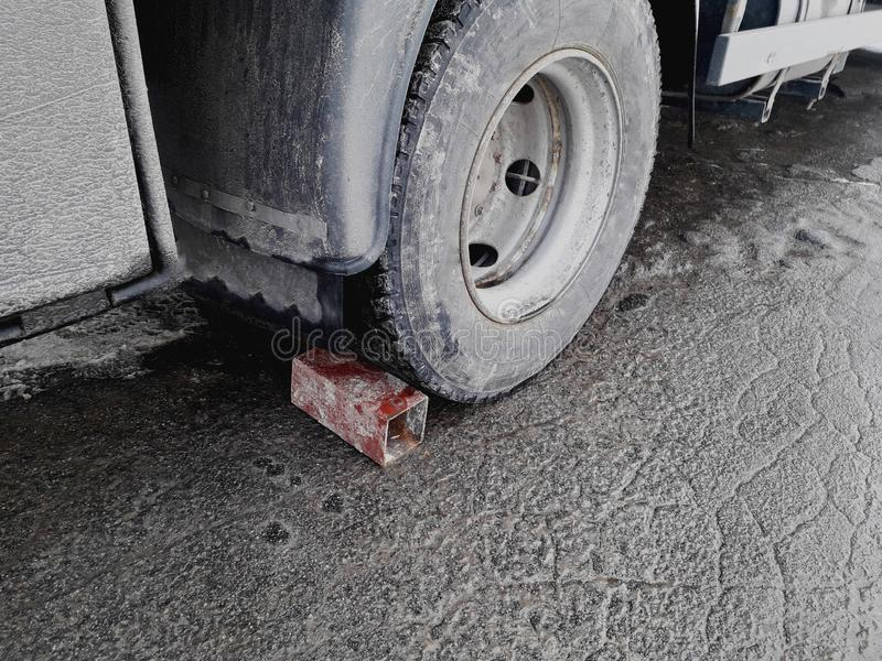 Brick under car wheel parking on slop way.Bad brakes on the truck. stock photo