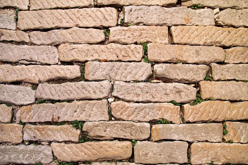 Brick vintage wall plastered with a stone close up / Part of architectural background, rustic materials and texture detail royalty free stock image