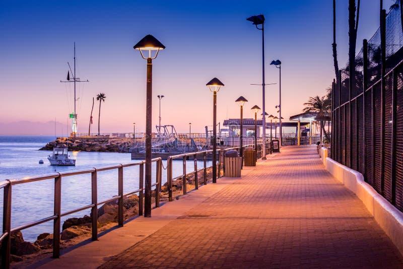 Brick walkway to boat dock in early sunrise light, streelights on, shadows, quiet, calm peaceful, Avalon, Santa Catalina Island, C stock image