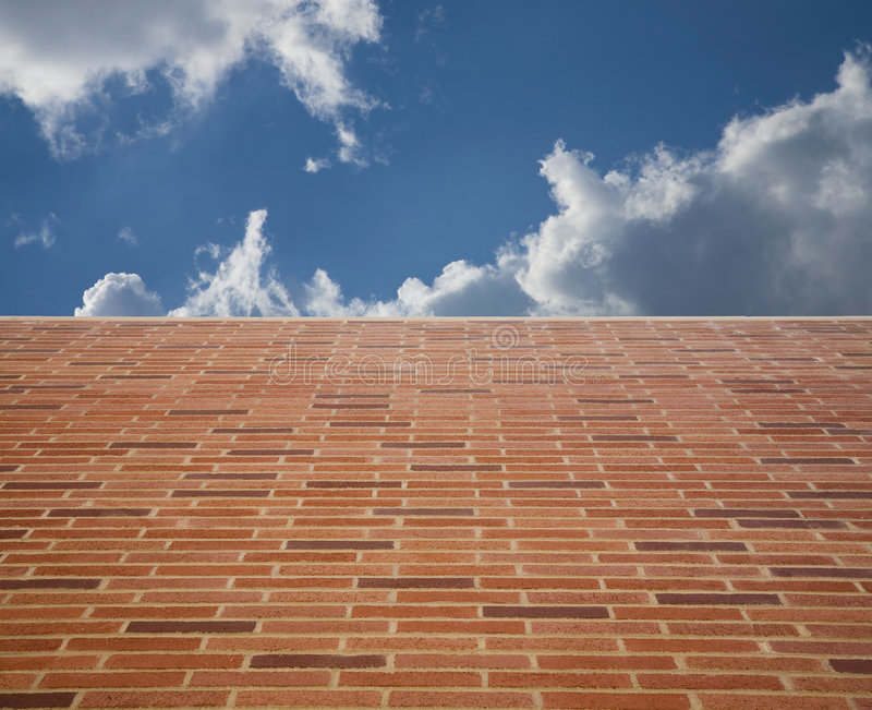 Brick Wall 10. Wide angle view looking up a brick wall towards a blue sky with clouds royalty free stock photo