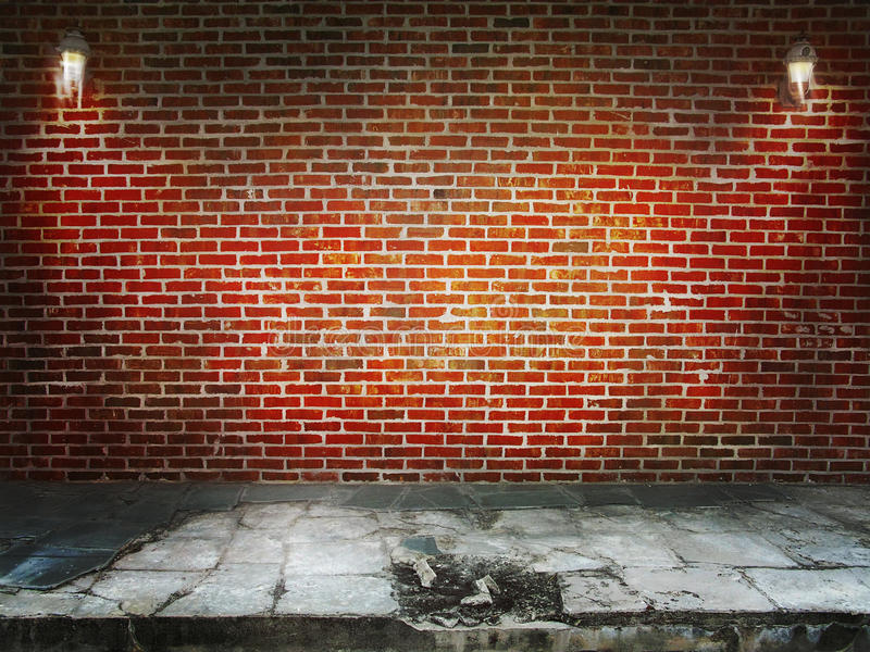 Brick wall. A brick wall with light fixtures with broken concrete flooring