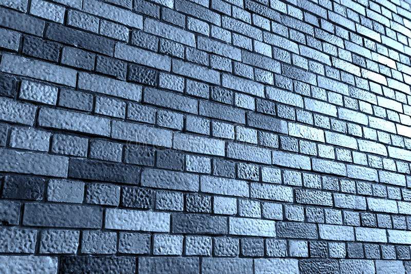 Brick wall. Angled view against a gray brick wall with additional light from the right royalty free stock photos