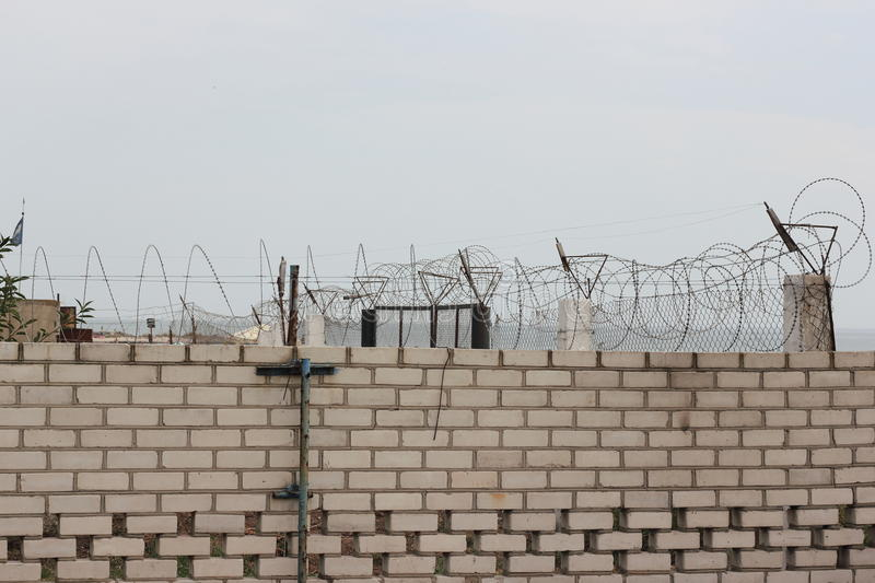 Brick Wall Behind Barbed Wire Stock Photo - Image of military, fence ...