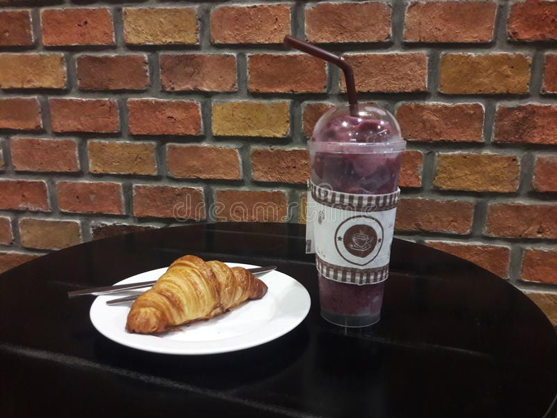 Brick wall and beverage and a croissant on table. Wallpaper or background of red brick wall and beverage and a croissant on the wooden table stock photo
