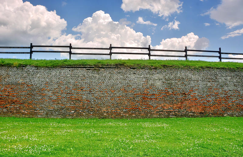 Brick wall and green grass. Brick wall with beautiful green grass, wood fence and blue cloudy sky royalty free stock image