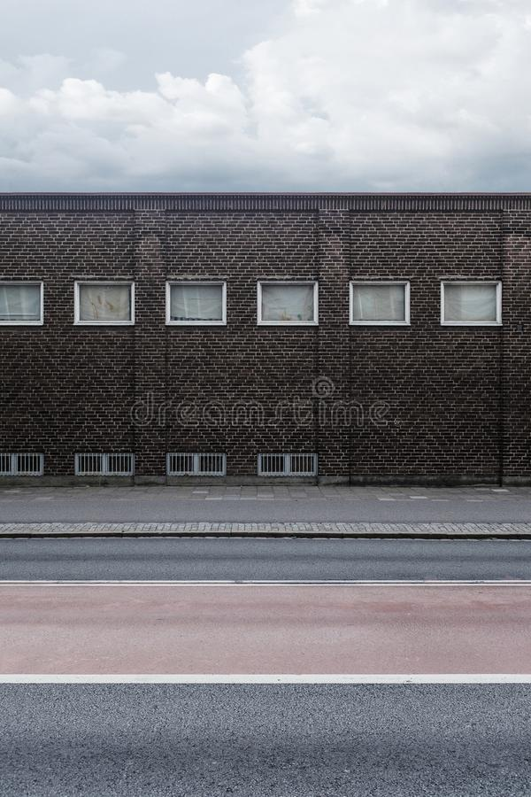 A brick wall of a building with little windows stock photo
