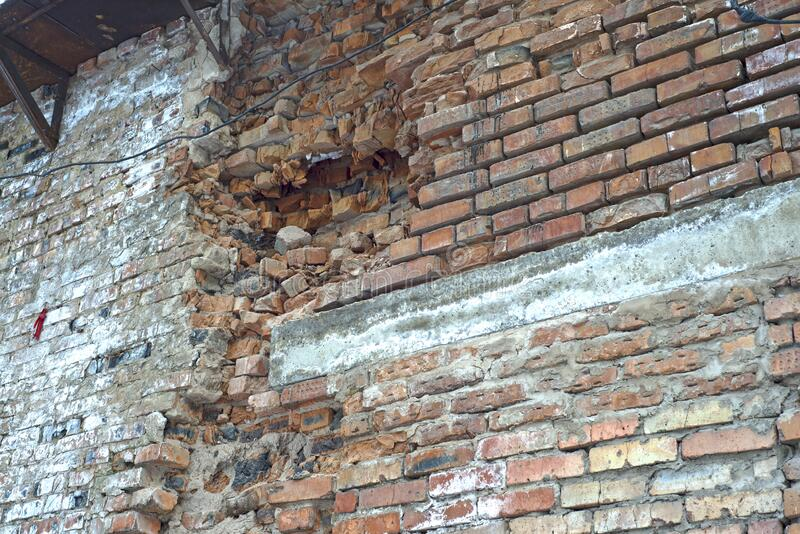 A brick wall collapses under natural conditions, in the open stock photography