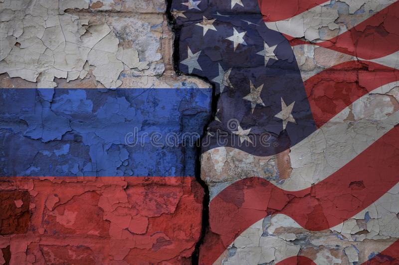 Brick wall with a crack painted on different sides in the American and Russian flags stock photography