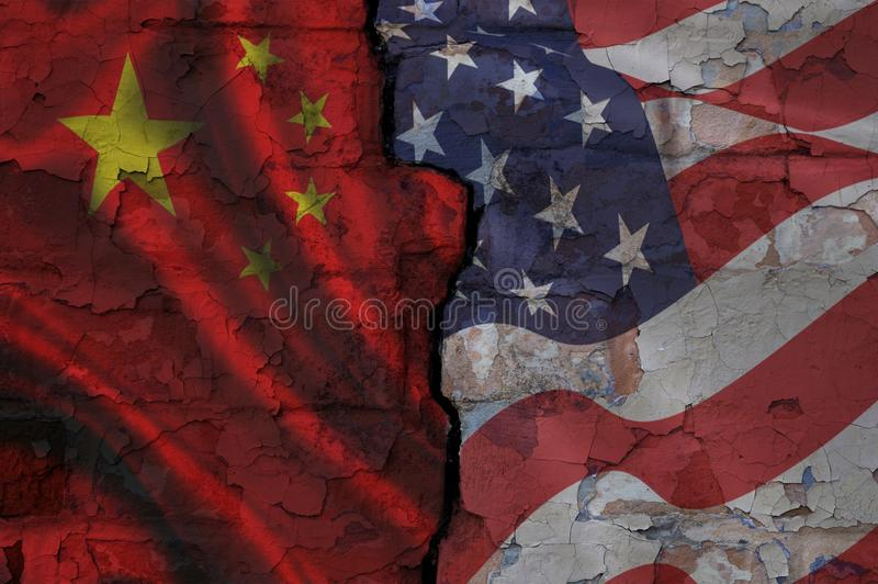 Brick wall with a crack painted on different sides in Chinese and American flags stock photography