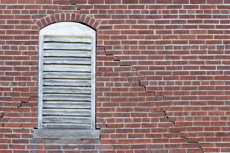 Brick wall cracked. An arched louver window in a cracked brick wall royalty free stock photography