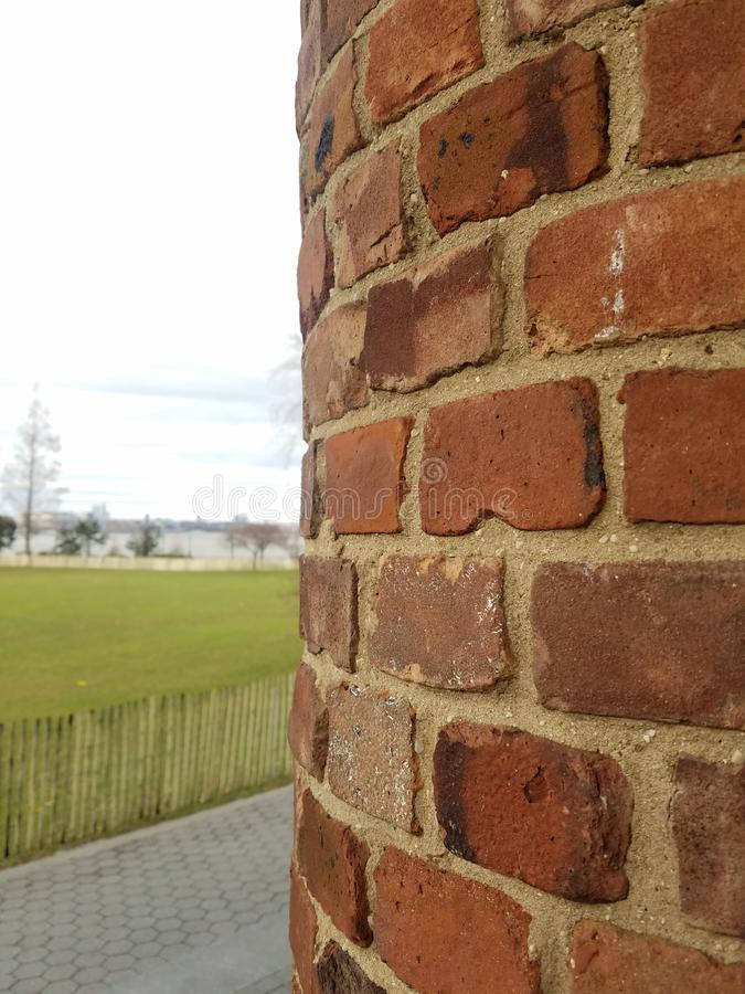Brick wall curved with park, foot path and distant Hudson river. Old curved brick exterior wall. Built structure. Parkland nearby. Hudson River park nyc. New stock photos