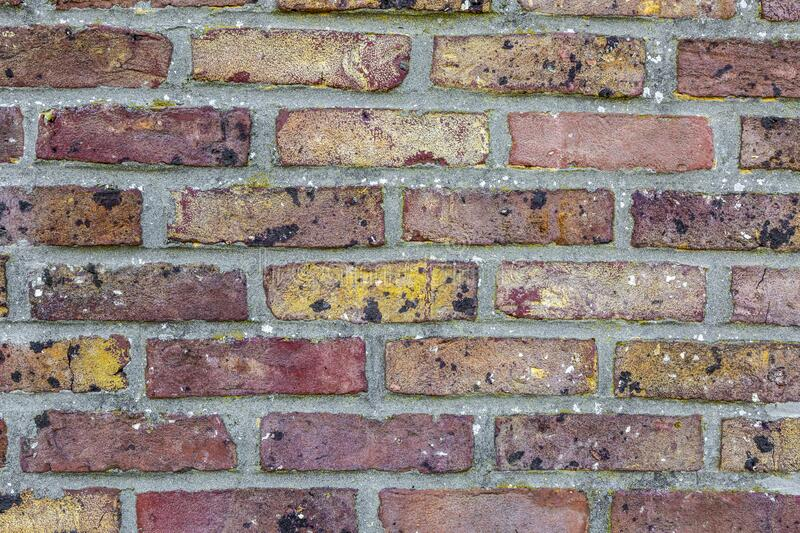 Brick Wall Detail. Close up image of a brick wall with weathered bricks in various colors royalty free stock image