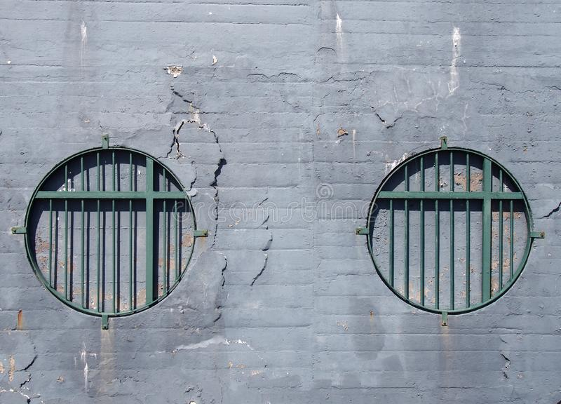 Brick wall with faded grey cracked peeling paint with two round blocked windows with green rusting metal bars. A brick wall with faded grey cracked peeling paint royalty free stock photos