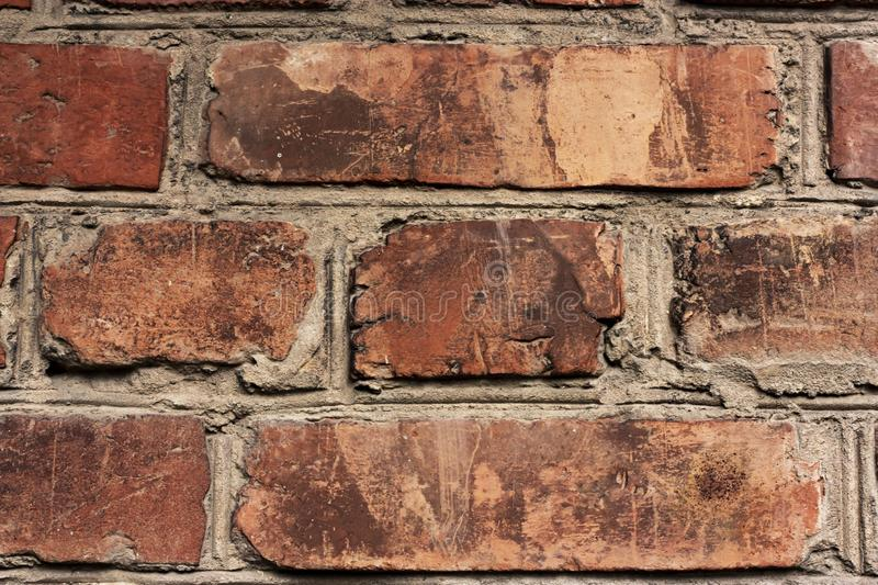 Brick wall fragment. Old dirty orange bricks with defects. Grunge texture with cracks and weathered. Brick wall fragment. Old dirty orange and red bricks with royalty free stock photography