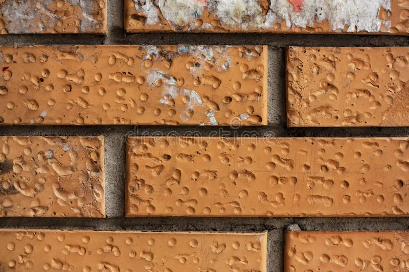 Brick wall fragment. Old dirty orange bricks with defects. Grunge texture with cracks and weathered. Brick wall fragment. Old dirty orange and red bricks with stock photography