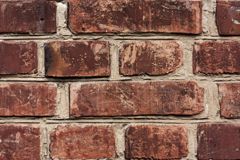 Brick wall fragment. Old dirty orange bricks with defects. Grunge texture with cracks and weathered. Brick wall fragment. Old dirty orange and red bricks with stock image