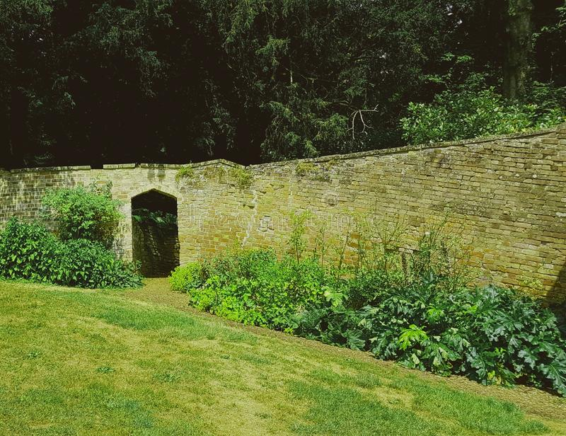 Brick wall with gateway. Brick wall in an area with trees grass and plants stock images