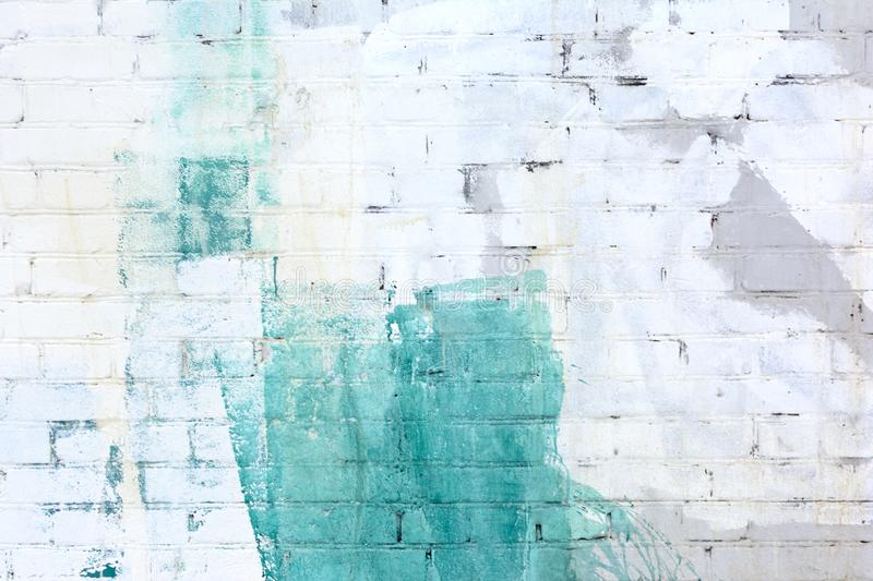 The brick wall is painted abstractly with white, gray and green paint. Background, texture. stock photo