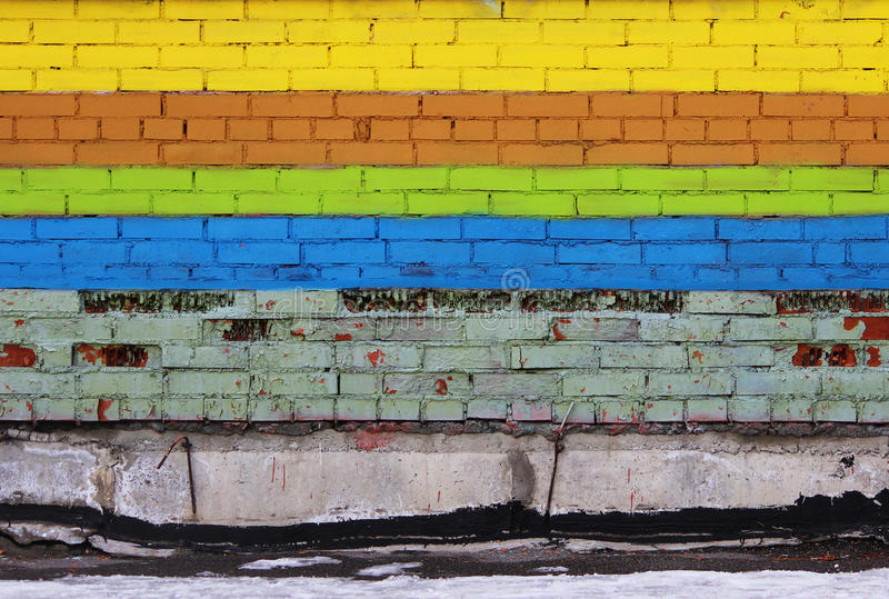 Brick wall painted with colored dyes in the form of stripes: yellow, brown, green and blue. Colorful brick wall painted with colored dyes in the form of stripes royalty free stock photo