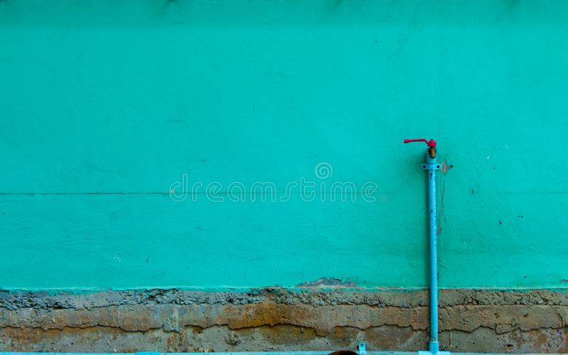 The Brick Wall Is Painted Green And A Faucet. Stock Image ...