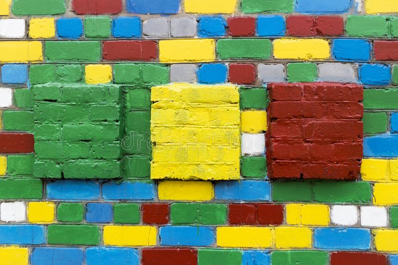 Brick wall with painted white, blue, green, red, yellow bricks. Brick wall with painted white, grey, blue, green, red, yellow bricks and large green, yellow, red stock photos