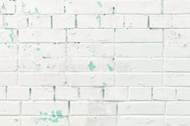 The brick wall is painted with white peeling paint, from under which an old layer of turquoise paint is visible. Photo stock photos