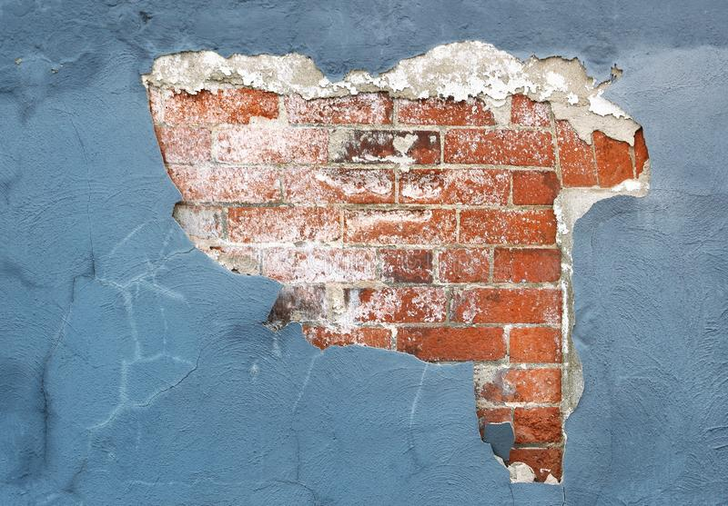 Brick wall with peeling paint and plaster in need of repair royalty free stock photo